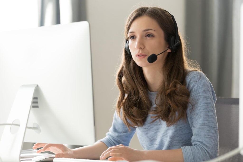 Businesswoman in headset call center agent consulting participating video conference